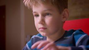Närbilddocka som skjutas av den gulliga lilla pojken som skriver på bärbara datorn som hemma koncentreras stock video
