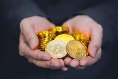 Närbilden av affärsman` s räcker mycket av bitcointecken av mynt - den finansiella handelrikedom för cryptocurrencyen och affärsi arkivbild