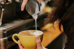 Närbilden av baristaen får latte-konst Arkivbild