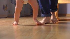 Närbilden av barn` s lägger benen på ryggen ta deras första steg arkivfilmer