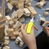 Närbilden av barn` s räcker att spela med träkonstruktörn, tegelstenar på tabellen Pojken limmar kvarter för att göra huset som b Royaltyfria Bilder