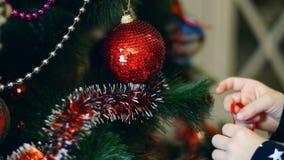 Närbilden av barnflickahänder dekorerar en julgran med ljusa färgrika julleksaker, bollar arkivfilmer
