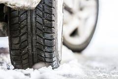 Närbilden av bilen rullar in vintergummihjulet på den snöig vägen arkivfoton