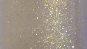 Närbilden av blänker att sväva i vodka Färgrik guld- målarfärg som blandar i vatten Virvla runt för FÄRGPULVER som är undervatten