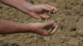 Närbilden av bonde` s räcker torkad jord för innehavet arkivfilmer