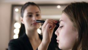 Närbilden av brunettkvinnan med ponnysvansen som applicerar skönhetsmedlet med en stor svart, utgör borsten Flicka i salongsminke lager videofilmer