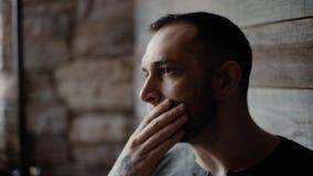 Närbilden av den brutala mannen med borstet och tatuerade händer som tänker slaglängder, vänder mot arkivfilmer