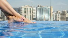 Närbilden av den härliga kvinnlign lägger benen på ryggen, fot, i taköverkantpöl med härlig stadssikt, mot en bakgrund av skyskra stock video