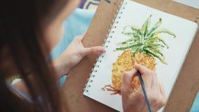 Närbilden av den kvinnliga handen med målarpenseln drar en ananas vid vattenfärger arkivfilmer