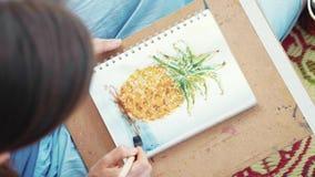 Närbilden av den kvinnliga handen med målarpenseln drar en ananas vid vattenfärger stock video