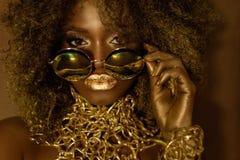 Närbilden av den kvinnliga modellen för den magiska guld- afrikanska amerikanen i massiv solglasögon med ljust blänker makeup som arkivbilder
