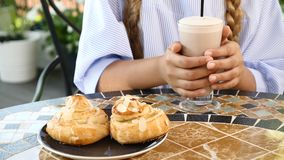 Närbilden av den kvinnliga ungen räcker hållande varm choklad Läcker homebaked bakelse på tabellen livsstil begrepp som ut äter lager videofilmer
