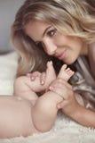 Närbilden av den lyckliga modern som kramar baby'sens fot hennes nyfött, behandla som ett barn gi Arkivbilder