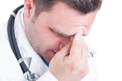 Närbilden av den manliga läkaren som trycker på hans panna som känsla, smärtar Fotografering för Bildbyråer