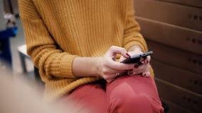 Närbilden av den unga kvinnan för händer i det orange omslaget använder en smartphone som sitter bland saker i en shoppa arkivfilmer