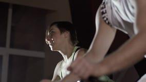 Närbilden av den unga kvinnan och en manridningövning cyklar lager videofilmer