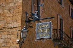 Närbilden av den utarbetade hotellplattan som gjordes av järn, klibbade i stenvägg och lampa i Orvieto royaltyfria foton