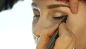 Närbilden av den yrkesmässiga sminkkonstnären som gör daglig makeup, sätter pulver på kvinnans kinder med borsten