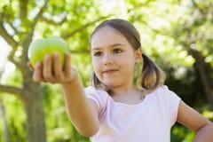 Närbilden av det hållande äpplet för flickan parkerar in Royaltyfri Fotografi