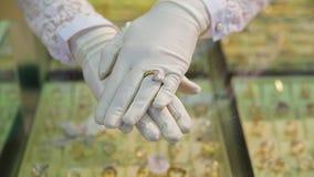 Närbilden av eleganta kvinnliga händer i vita handskar visar att guld- härliga cirklar shoppar in bak räknare med smycken