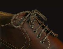 Närbilden av en brunt skor på svart Royaltyfri Foto