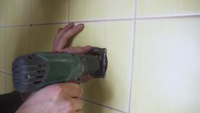 Närbilden av en elektriker med en skruvmejsel som seting upp ett vitt uttag, begreppet av elektrifiering av rummet, är lager videofilmer