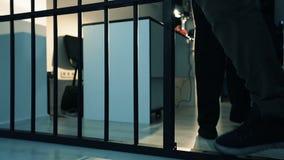 Närbilden av en fot för polis` s leder lagbrytaren in i fängelsecellen lager videofilmer