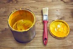 Närbilden av en gul målarfärg kan och borsten Royaltyfri Bild