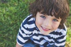 Närbilden av en gullig pojke som ler på, parkerar arkivfoton