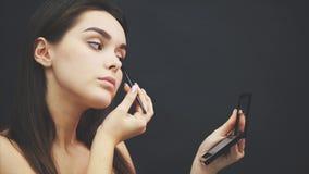 Närbilden av en härlig framsida av en ung flicka får en makeover Kvinna som applicerar en ögonskugga på hennes ögonbryn vid borst arkivfilmer