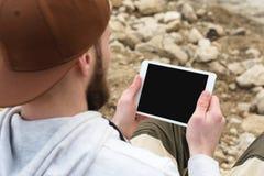 Närbilden av en hord i ett brunt lock i den öppna luften rymmer en vitminnestavlaPC i hans händer En skäggig man ser arkivfoton