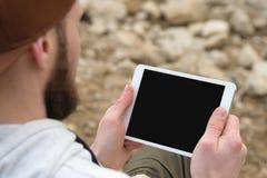 Närbilden av en hord i ett brunt lock i den öppna luften rymmer en vitminnestavlaPC i hans händer En skäggig man ser arkivbilder