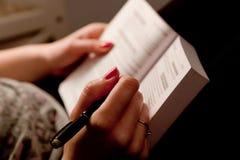 Närbilden av en kvinna räcker att ta anmärkningar i en bok, medan studera hemma Arkivbilder