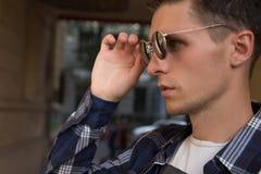 närbilden av en man, som tar av hans solglasögon, den manliga ståenden i profil, var han rymmer exponeringsglas, trycker på expon royaltyfria bilder