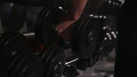 Närbilden av en man tar en hantel i idrottshallen arkivfilmer