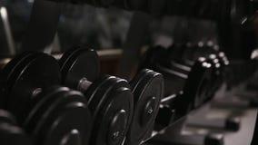 Närbilden av en man tar en hantel i idrottshallen stock video