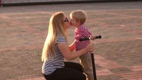Närbilden av en moder med hennes son som går i en stad, parkerar i sommaren på solnedgången arkivfilmer