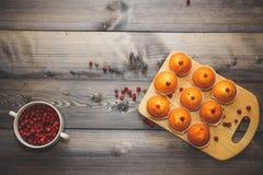 Närbilden av en muffin bakade nytt dekorerat med röda bär på ett ljust - den gråa trätabellöverkanten på en skärbräda royaltyfria foton