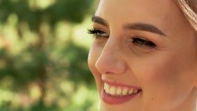 Närbilden av en positiv ung härlig kvinnabrud ser bort lager videofilmer
