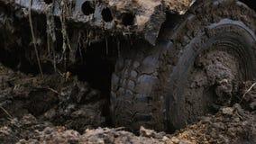 Närbilden av ett bilhjul klibbade i gyttjan Hjulet rotera, men det som är hjälplöst arkivfilmer