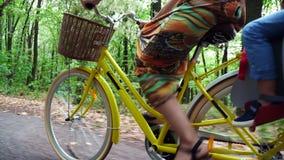 Närbilden av ett cykelhjul, medan köra, kvinnlig fot, vrider pedaler en kvinna i en klänning, med en korg av blommor lager videofilmer