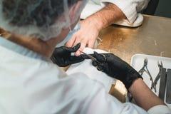 Närbilden av ett manikyristCutting Off The nagelband från person`en s fingrar royaltyfria foton