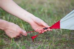 Närbilden av flickahänder fäster ett tält för campa pinnor Royaltyfria Foton