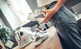 Närbilden av flickan i sko shoppar väljer gymnastikskor arkivbilder