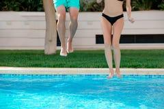 Närbilden av flickan och pojken lägger benen på ryggen banhoppning in i en simbassäng Royaltyfri Bild
