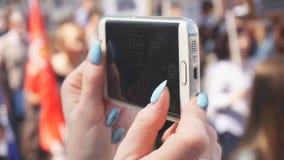 Närbilden av flickans händer tar av på smartphonen en stor folkmassa av folk som går ner gatan arkivfilmer