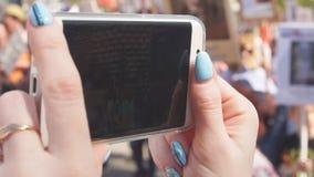 Närbilden av flickans händer tar av på smartphonen en stor folkmassa av folk som går ner gatan, ultrarapid arkivfilmer
