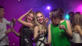 Närbilden av flickor dansar med exponeringsglas av champagne långsam rörelse lager videofilmer