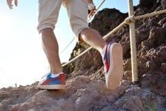 Närbilden av fotvandraren lägger benen på ryggen trekking längs en stenig bana Royaltyfri Foto