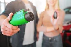 Närbilden av grön elektrisk uppladdning pluggar i handen, elbilbegrepp Nyckel- hållande bil för kvinna Ung le familj royaltyfria bilder